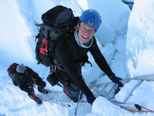 Paul climbs a ladder on the way down through the icefall. Photo Fiona Adler.
