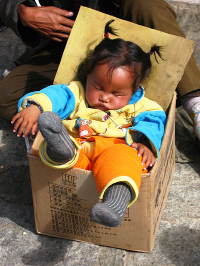 A child seems to be comfortable sleeping in a cardboard box outside a monastery as her mother sells jewellery.