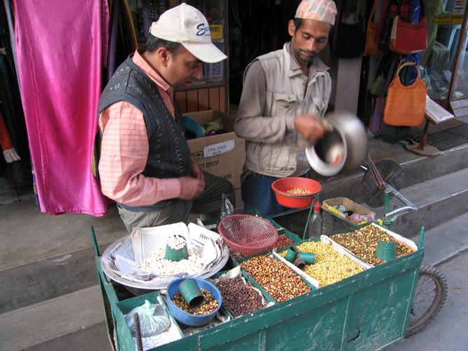A street vendor selling hot nuts in Thamel, Kathmandu briskly washes a pot while closely watched by a prospective customer. Photo Paul Adler