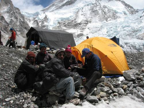 Ptemba pays our porters that have carried our gear into base camp. Photo Paul Adler.