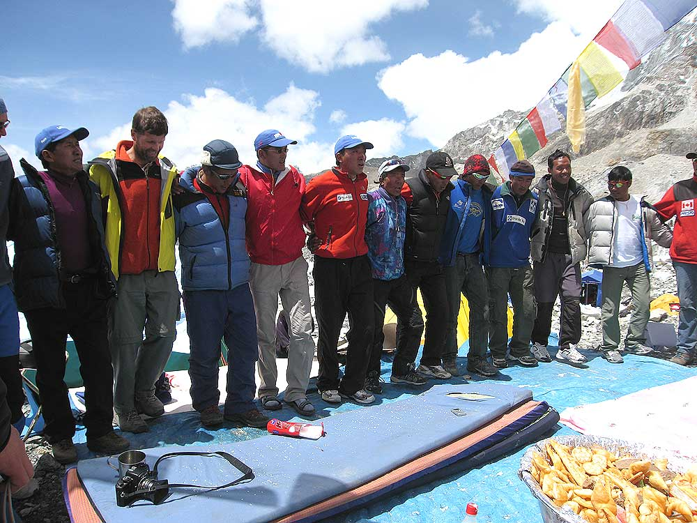 Sherpas and team members dance around the altar during the puja ceremony at Everest base camp in 2007. Our leader, Pertemba Sherpa is on the left wearing the blue cap. Photo Paul Adler.
